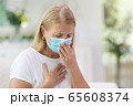 Sick woman in face mask. Ill senior coughing. 65608374