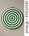 Portrait of dartboard with numbers against concrete wall 65614385