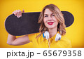Cheerful young woman with skateboard 65679358