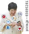 携帯電話でSNSを楽しむ女性 65695281