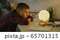 Boy changing color of table lamp 65701315