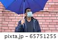 Sad man in mask standing alone under the umbrella, social distance, self isolation, quarantine 65751255