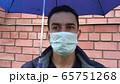 Sad man in mask standing alone under the umbrella, social distance, self isolation, quarantine 65751268