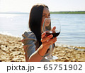 beautiful girl on the beach drinking red wine. 65751902