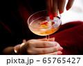 スパークリングワインにグミを漬ける女性 65765427