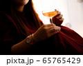 窓際でスパークリングロゼワインを飲む女性 65765429