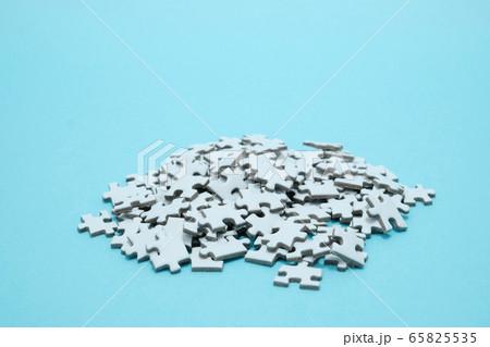 ステイホームで集中力アップの為の水色背景に置かれた山積みになった無地のジグソーパズル 65825535