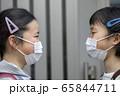 マスク姿で向かい合う小学生 通学 登校 65844711
