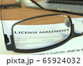 Copy of a license agreement behind glasses on a desk, 3D rendering 65924032