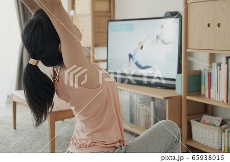 家で動画を見ながらヨガをする女性 おうちヨガ 家でヨガをする女性  65938016