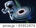 Astronaut near colourful Black hole somewhere in space.  65952874