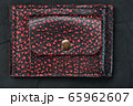 Red and black leather wallet on a black 65962607