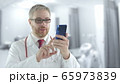 Male doctor uses his phone for a video call from patient 65973839