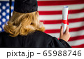 Graduate with a diploma against the background of the U.S. flag. View from behind 65988746