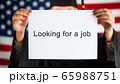 A graduate in a mantle and cap is holding a poster about job search. Employment in the USA 65988751