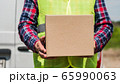 Courier with cardboard box in hand stands against the background of the delivery service van 65990063