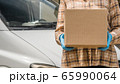 Courier with cardboard box in hand stands against the background of the delivery service van 65990064