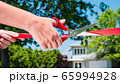 Hand with scissors cuts red ribbon in the background of new house 65994928