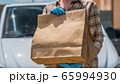 Delivery service employee holds paper bags with food on a white van background. Food delivery during the epidemic 65994930