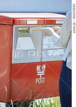 郵便ポストに封筒を入れる若い女性の手元 66029885
