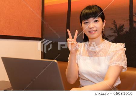 ノートパソコンの前でピースサインする女性 66031010