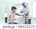フェイスシールドをして防護服を着た医療従事者が陽性患者に投薬のワクチン注射をうつ 66123171
