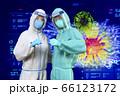 フェイスシールドをして防護服を着た医療従事者がガッツポーズをしウイルスと戦う意志を表している 66123172