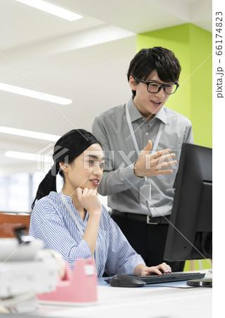 ビジネスシーン PCモニタを見て話をする若い男女のオフィスワーカー 66174823