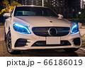 夜のドライブイメージ(白いスポーツセダン車と街並み夜景) 66186019