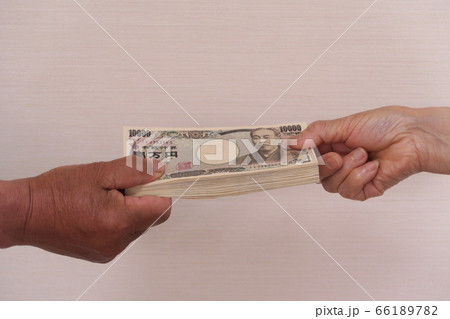 100万円を手渡す(男性と女性の手) 66189782