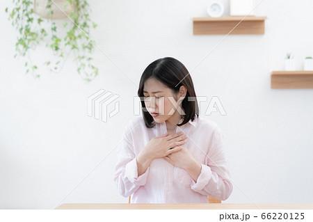 息苦しさを感じて胸を押さえる女性 66220125