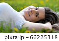 Woman lies on green grass, relaxing outdoors looking happy and smiling 66225318
