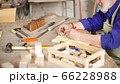 Bearded carpenter with gray hair works with wooden workpieces 66228988