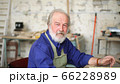 Portrait of gray-haired carpenter in workshop with various tools for manual work 66228989