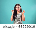 Beautiful girl with an enthusiastic expression on her face posing on blue background 66229019