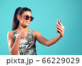 Pretty girl smiles broadly while taking a selfie on her phone 66229029