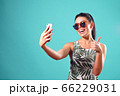 Happy girl posing in Studio taking a selfie on the phone 66229031