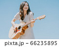 Beautiful woman playing guitar on blue sky background 66235895