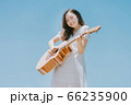 Beautiful woman playing guitar on blue sky background 66235900