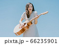 Beautiful woman playing guitar on blue sky background 66235901