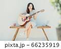 A beautiful woman playing guitar 66235919