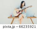 A beautiful woman playing guitar 66235921