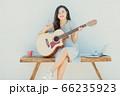 A beautiful woman playing guitar 66235923