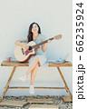 A beautiful woman playing guitar 66235924