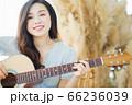 Beautiful woman playing guitar at home 66236039