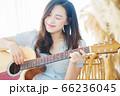Beautiful woman playing guitar at home 66236045