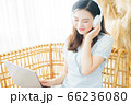 Beautiful woman wearing headphone and using laptop at home 66236080