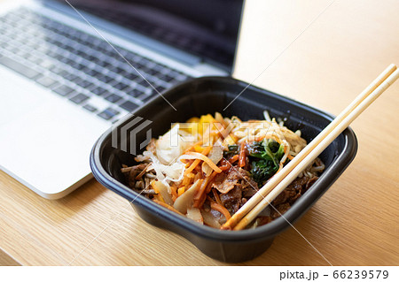 ノートパソコンの隣に置いたビビンバ丼 66239579