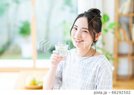 リビングでミネラルウォーターを飲む若い女性 66292502