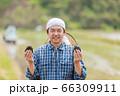 田んぼでおにぎりを持つ男性 66309911